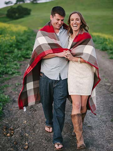 Couple walking side by side wrapped around with a plaid blanket. Engagement photography
