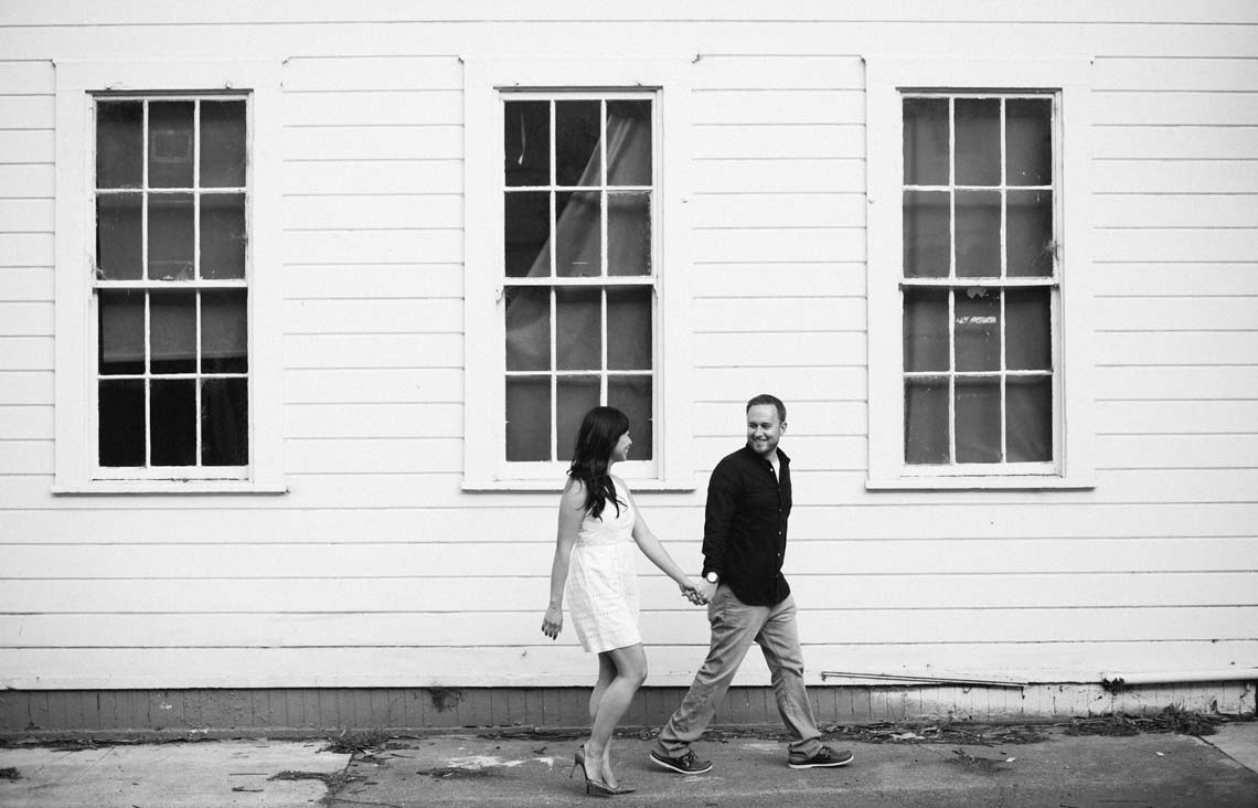 Black and White image of couple walking in front of an old civil war era building