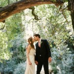 Romantic photo of bride and groom. Couple kissing underneath a tree.