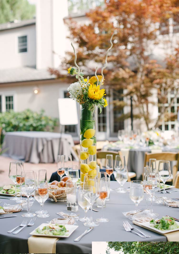 Wedding reception details: Table, glasses, plates and centerpiece with lemons and yellow flowers