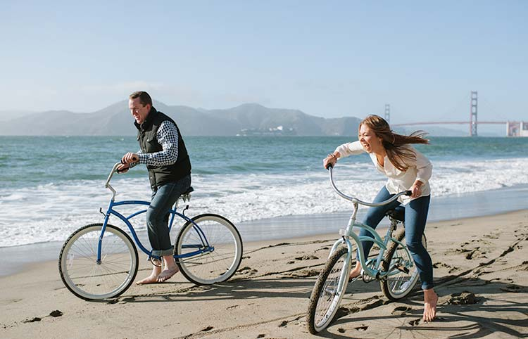 Fun engagement photos at Chine Beach in San Francisco. Couple riding bikes on the beach.