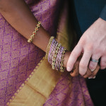 Multicultural wedding - bride wearing sari and jewelry holding groom's hand.